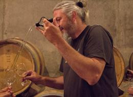 樽から直接試飲用のワインをピペットで取り出すアルノー